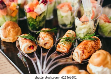 Beautifully decorated catering banquet table with salads and profiteroles. Variety of tasty delicious snacks on the table