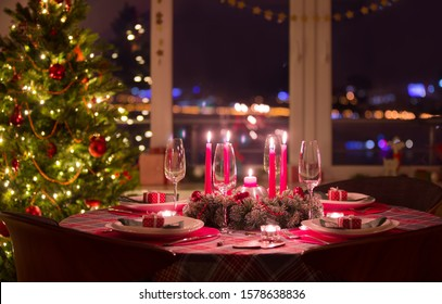 beautifully decorated Christmas table with candles and glasses near the Christmas tree
