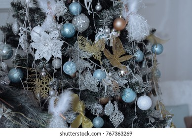 Beautifully decorated Christmas tree with colorful toys, snowflakes, crackers, and garlands.