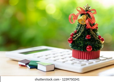 A beautifully decorated Christmas tree placed on a white calculator and with a miniature book. Christmas concept celebrated on December 25 every year.