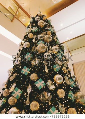 beautifully decorated christmas tree with a lot of silver and gold balls diamond gift