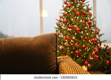 A beautifully decorated christmas tree, standing behind a brown, cozy couch. Cold winter light is entering through the windows. Concept about a lazy, warm indoor day at home during christmas holidays.
