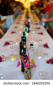 A beautifully decorated dinner table with glassware, cutlery and napkins on a white tablecloth is set for a grand party. Twinkle lights are in the room while guests mingle in the background.