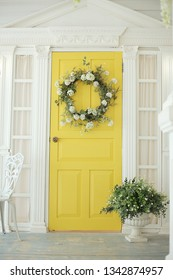 Beautifully decorated farmhouse look. Bright yellow door, a spring greenery wreath of flowers, a pot with green plants. Rustic interior element of spring porch