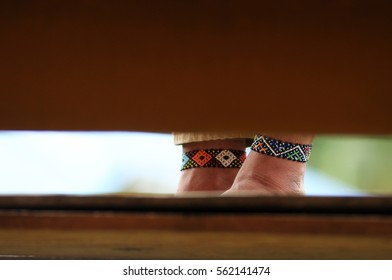 Beautifully decorated foot with native Sarawak beads bangles seen in between woods wall.