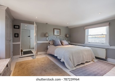 Beautifully decorated master bedroom within a renovated cottage with wrought iron style bed contemporary shades of white and grey, bed dressed with oversized cushions, rugs, built in wardrobe.