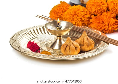 Beautifully Decorated Pooja Thali for festival celebration to worship, huldi or turmeric powder and kumkum, flowers, scented sticks in brass plate, hindu puja thali