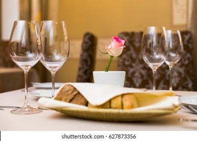 Beautifully decorated table in the restaurant. On the table is a vase with pink rose