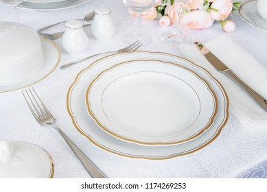 Beautifully decorated table with white plates, glasses, cutlery and pink flowers on luxurious tablecloths