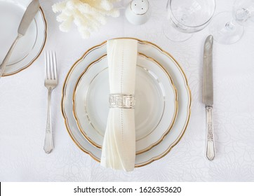 Beautifully decorated table with white plates, glasses, antique cutlery and white coral on luxurious tablecloths