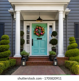 Beautifully decorated turquoise colored front door of traditional home. Brick path and trimmed hedges.