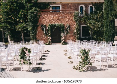 a beautifully decorated wedding ceremony, a floral wedding arch and chairs