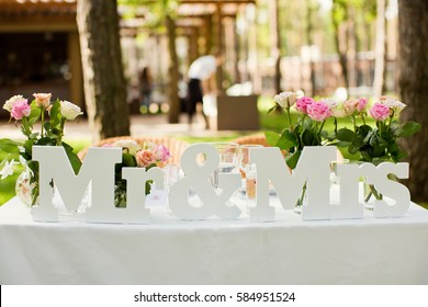 Beautifully decorated wedding table with flowers and MR and MRS letters