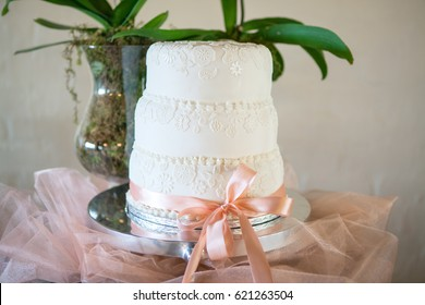 Beautifully decorated white wedding cake on a table with peach-colored ribbon tied around it