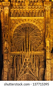 Beautifully detailed gable and rose window above the massive central portal of the west facade of Strasbourg Cathedral at twilight.