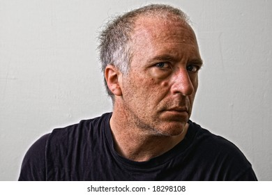 beautifully detailed real portrait of weathered looking adult white man staring intensely at the viewer with head turned away