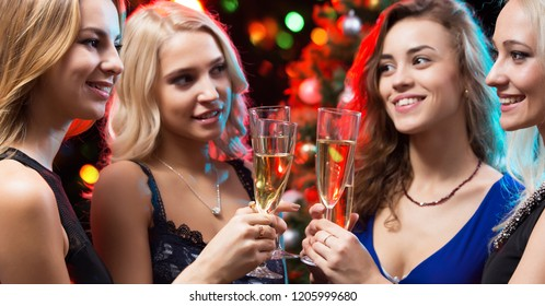 Beautifully dressed young girls with glasses of champagne at a Christmas party