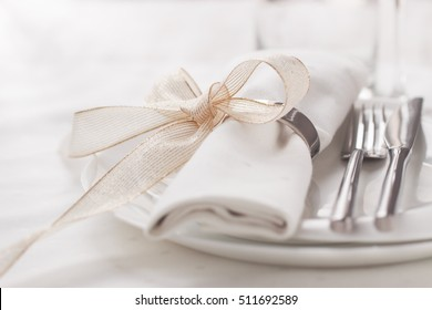 Beautifully elegant decorated table for holiday - wedding or valentine day with modern cutlery, bow, glass, candle and gift, closeup, toned