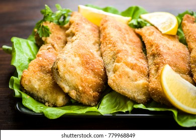 Beautifully fried pieces of carp on a black plate