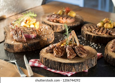 Beautifully grilled lamb rib chops, beef steaks, meatballs and sirloin, medium rare with fried potato chips on wood serving board.