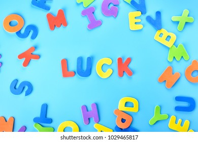Beautifully laid out inscription luck of multi-colored letters. Blue background.