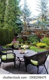 Schöner landschaftlicher Garten mit andauernden Blumen und immergrünen Bäumen. Im Freien sitzend in einem Garten, umgeben von einem Zedernwald in Kanada. Auch in horizontaler Richtung verfügbar.