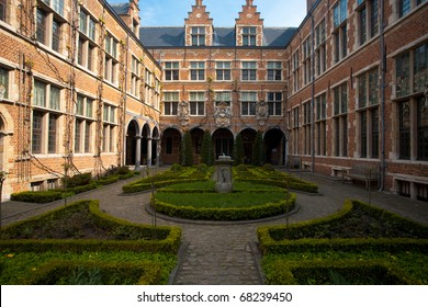 A beautifully manicured European courtyard garden surrounding by three sides of old world brick facade in Antwerp, Belgium