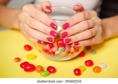 Beautifully manicured fingernails with fuchsia nail polish on a yellow background with a bowl of multicolored candies.