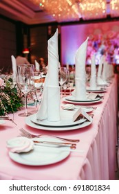 Beautifully organized event, glasses at served festive white table ready. Banquet, wedding decor, celebration. Cutlery and crockery