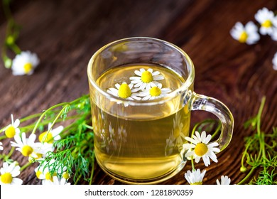 Beautifully prepared cup of real fresh camomile tea prepared on a vintage wooden board