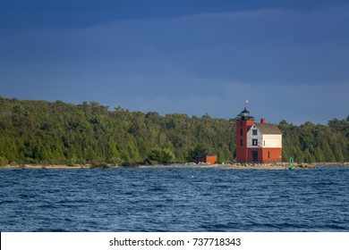 Beautifully restored Historic Round Island Lighthouse on Mackinac Island Michigan. Its bright colors stand out dramatically surrounded by the blue waters and pine tree forest  of Lake Huron.
