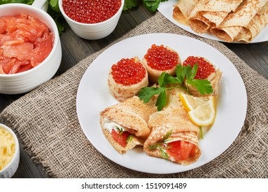 Beautifully rolled pancakes(blini) with fresh sour cream, red caviar and red fish on a white plate. Around a plates with fish, caviar, and fresh butter. Holiday. Maslenitsa. Rustic style, close up vie