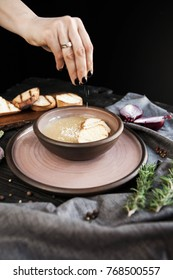 Beautifully served onion soup with croutons on a wooden dark table