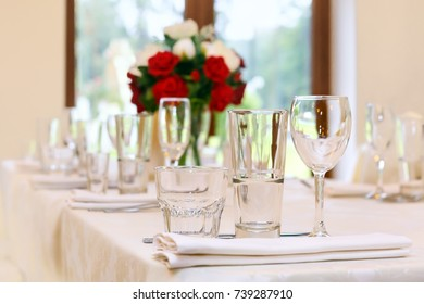 Beautifully set festive table, decorated with a bouquet of roses. The preparations for the party. Glasses in the foreground. Soft focus, selective focus