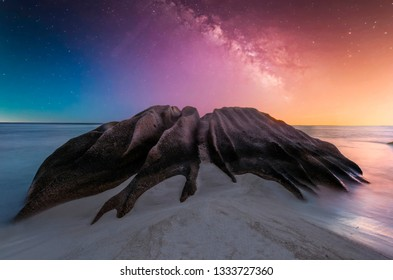 Beautifully shaped granite boulder is washed by sea at Anse Source d'Argent beach, La Digue island, Seychelles.Night time with stars