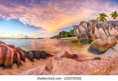 Beautifully shaped granite boulders and a dramatic sunset  at Anse Source d'Argent beach, La Digue island, Seychelles. Panorama