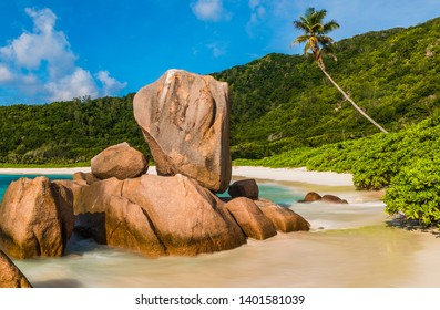 Beautifully shaped granite boulders in the turquoise sea (daytime long exposure technique) and a perfect white sand at Anse Coco, La Digue island, Seychelles