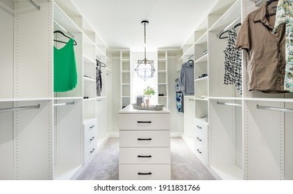 beautifully staged walk in closet with custom white cabinets