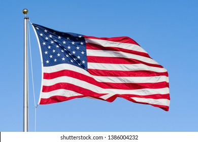 Beautifully waving star and striped American flag a blue sky background; Close Up for Memorial Day or 4th of July