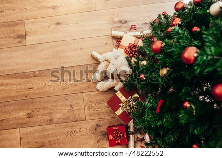 Beautifully wrapped Christmas gifts and  Christmas crackers placed beside a Christmas tree. Christmas background with decorations and gift boxes on wooden floor.
