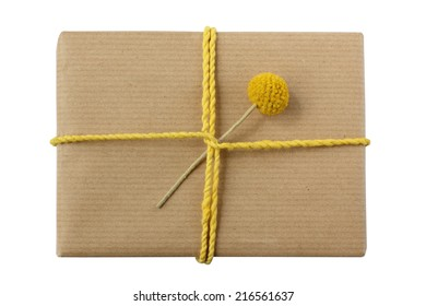 Beautifully wrapped gift - eco-friendly kraft paper decorated with yellow twine and flower - isolated on white