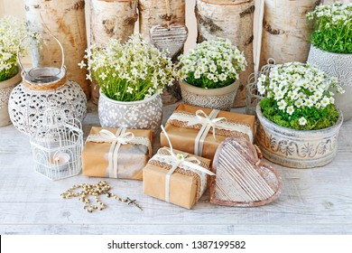 Beautifully wrapped gifts for the first communion, rosary and floral decoration in the background.