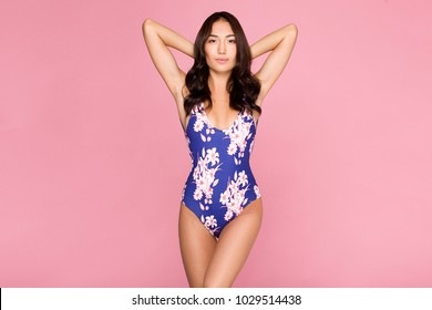 Beautiful,Sexy asian girl standing on pink background in a colors bathing suit bikini and smiling.perfect for photo advertisements, style vogue