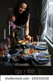 Beautifulspring table fulls of fruit, cinnamon buns and red wine on rustic dark background. Serve table. Romantic dinner. Woman holds juice, cinnamon bun