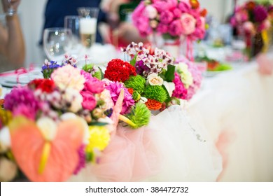 Beautifuly decorated wedding reception table covered with fresh flowers closeup