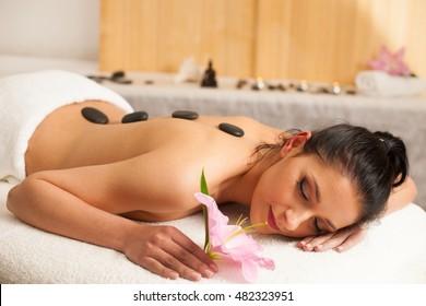 Beautifulyoung woman having a rejuvenating massage in a wellness studio - spa