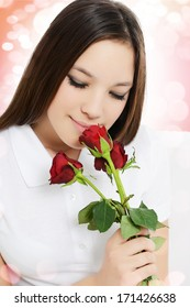Beautiful,young woman smells a bouquet of roses flowers