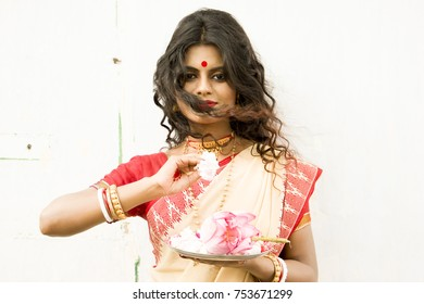 Beautirul Indian female model wearinng an off white and red saree