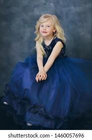 beautiuf blond little girl in navy blue dress