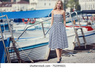 beautty fashion portrait of blonde woman stripped dress. Fashion portrait. Smiling blonde woman in fashionable look. Sea style. sea quay with boats